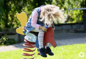 Ein Mädchen wippt auf einem Spiel-Tier
