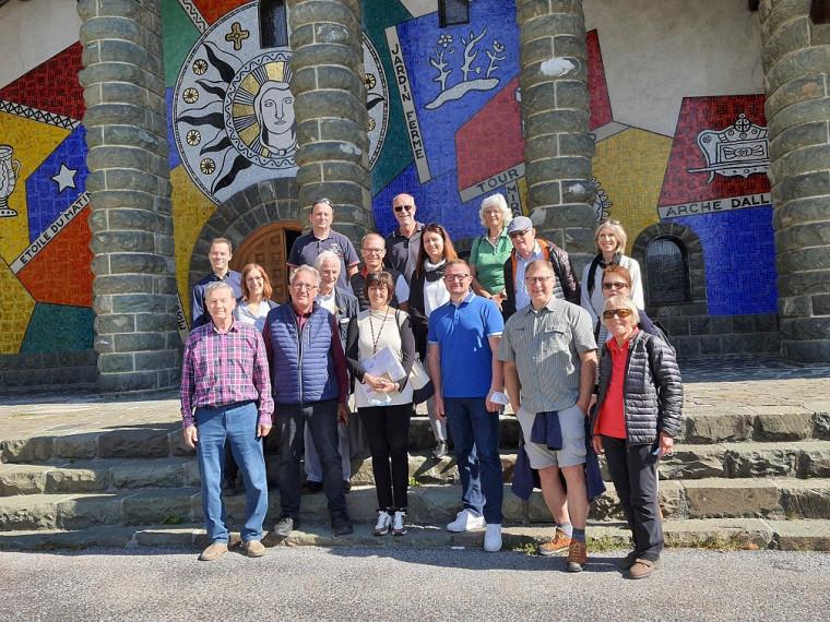 Die Pfullinger Delegation steht versammelt vor dem Eingangsportal der Kirche, im Hintergrund sind die Treppe hinauf zum Eingang, vier steinerne Säulen und eine großflächige Wandmalerei zu in blau, rot und gelb zu sehen.