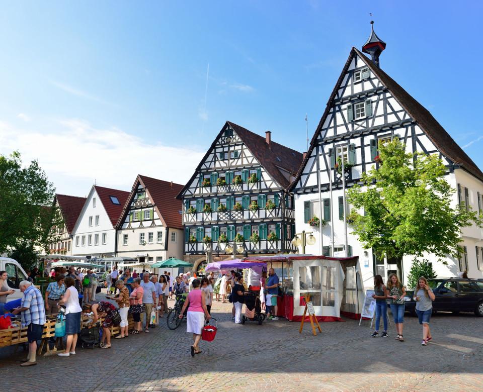 Fachwerkhäuser im Ortskern von Pfullingen mit Markttreiben und Menschen im Vordergrund