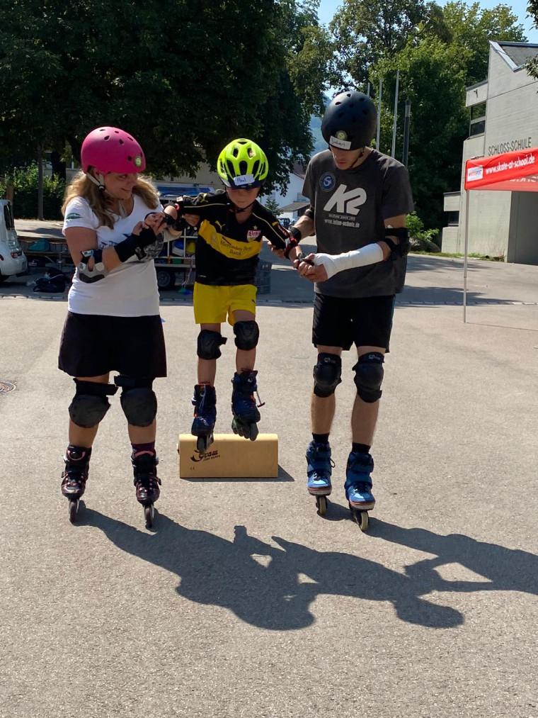 Kleiner Junge springt mit Hilfe von Mitarbeitern der Inline Skate Akademie über eine Schanze