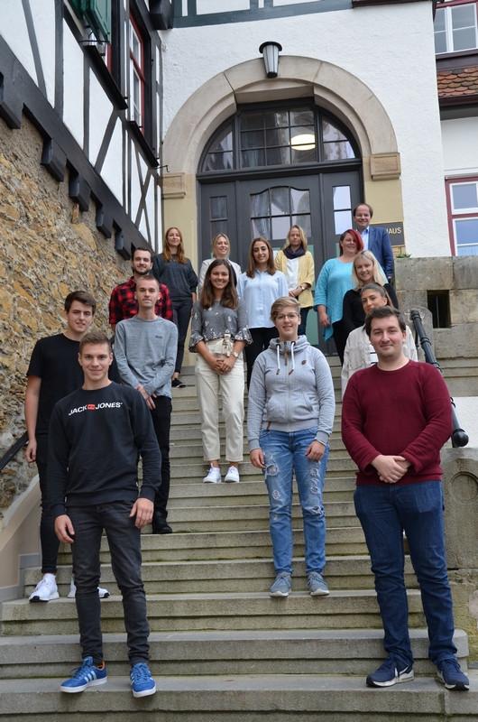 Die zwölf neuen Auszubildenden auf der Treppe des Rathauses Zwei